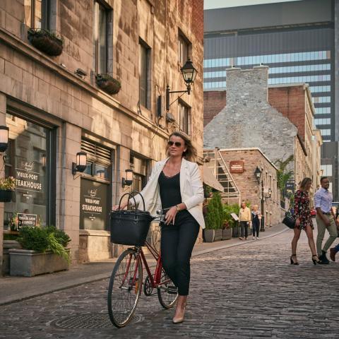 person walking their bike down a cobblestone street