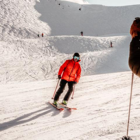 person in an orange jacket skiing